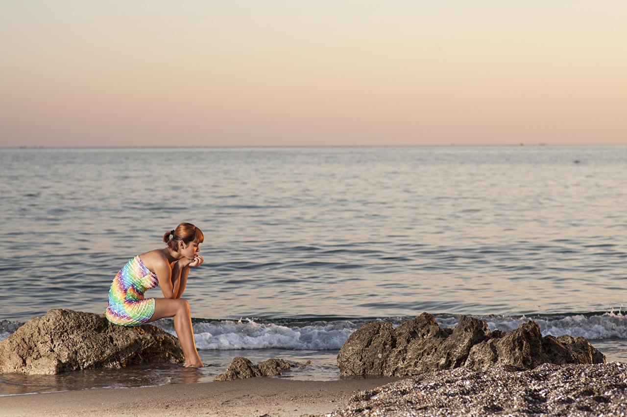 Обои для рабочего стола Море молодая женщина Рассветы и закаты Сидит Камень Платье девушка Девушки молодые женщины рассвет и закат сидя Камни сидящие платья