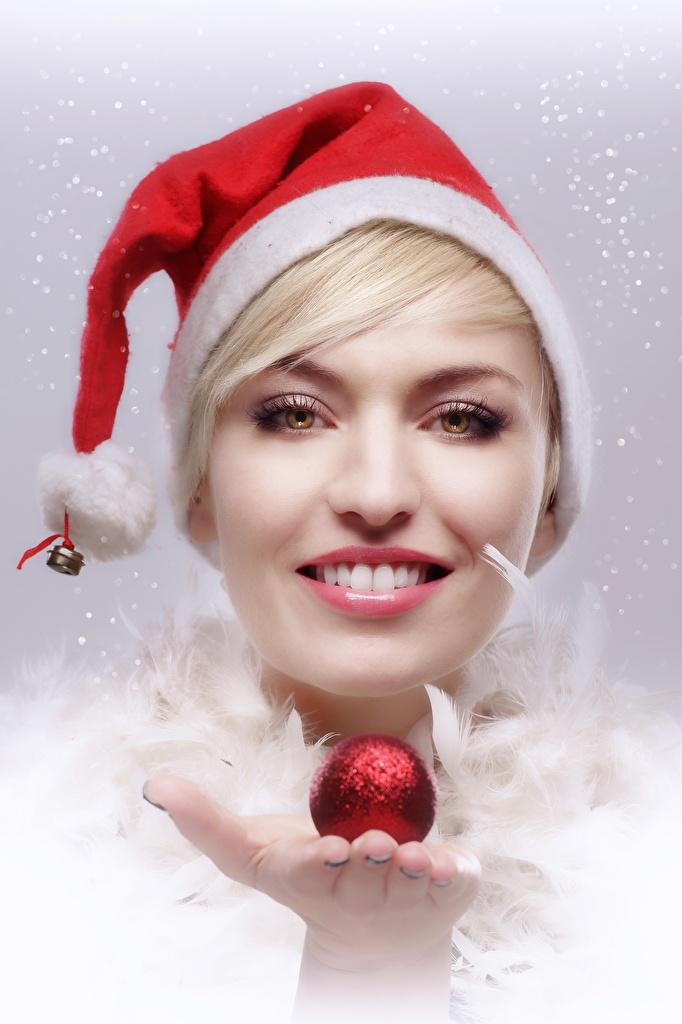 Фотографии Новый год Блондинка Улыбка Шапки Девушки Руки Шарики смотрит Рождество Шар Взгляд