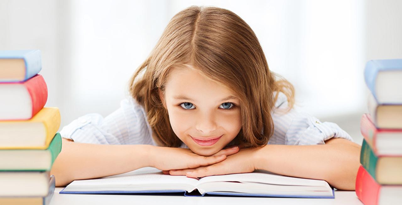 Картинка Девочки Школа Шатенка Улыбка Ребёнок Волосы Книга Взгляд школьные Дети смотрит