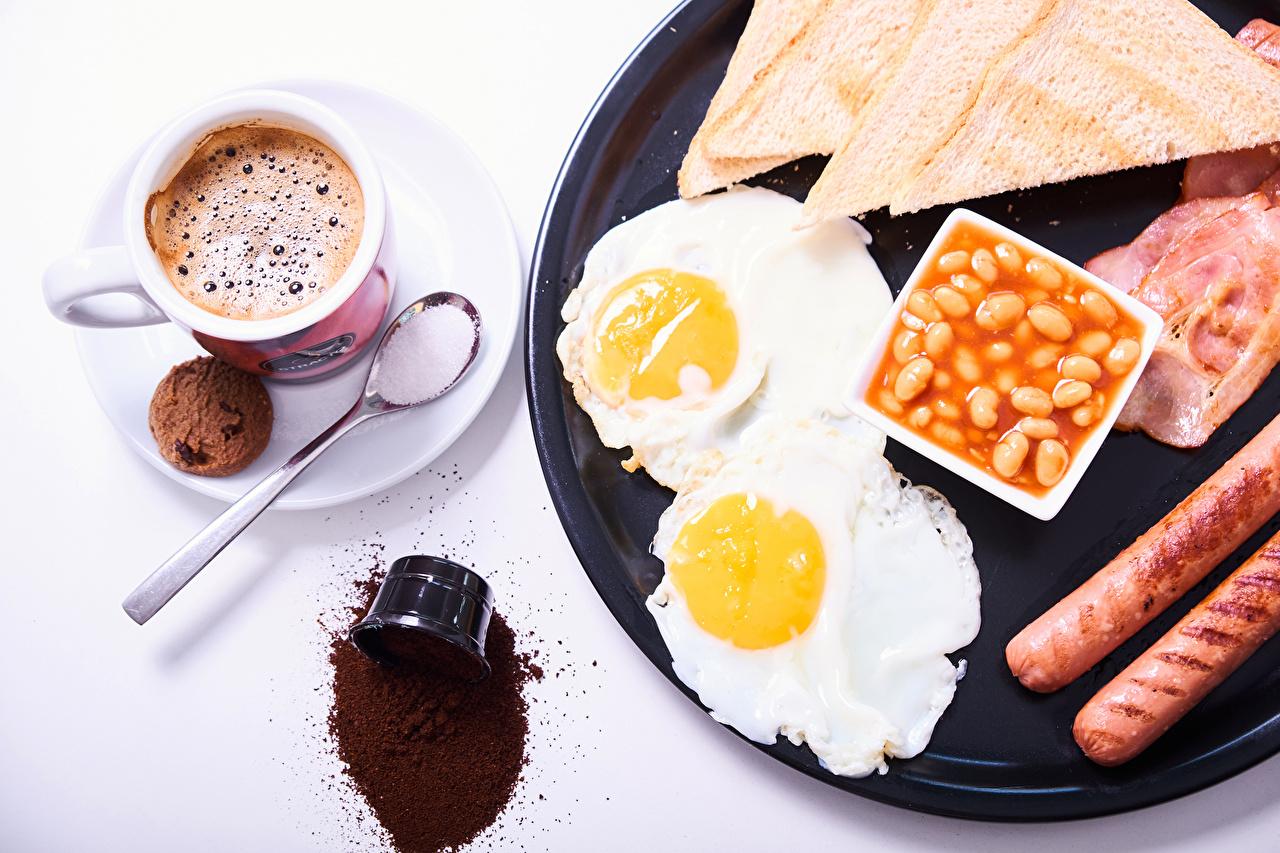 Фото Яичница Кофе Завтрак Хлеб Сосиска Чашка Печенье Продукты питания Белый фон яичницы глазунья Еда Пища чашке белом фоне белым фоном
