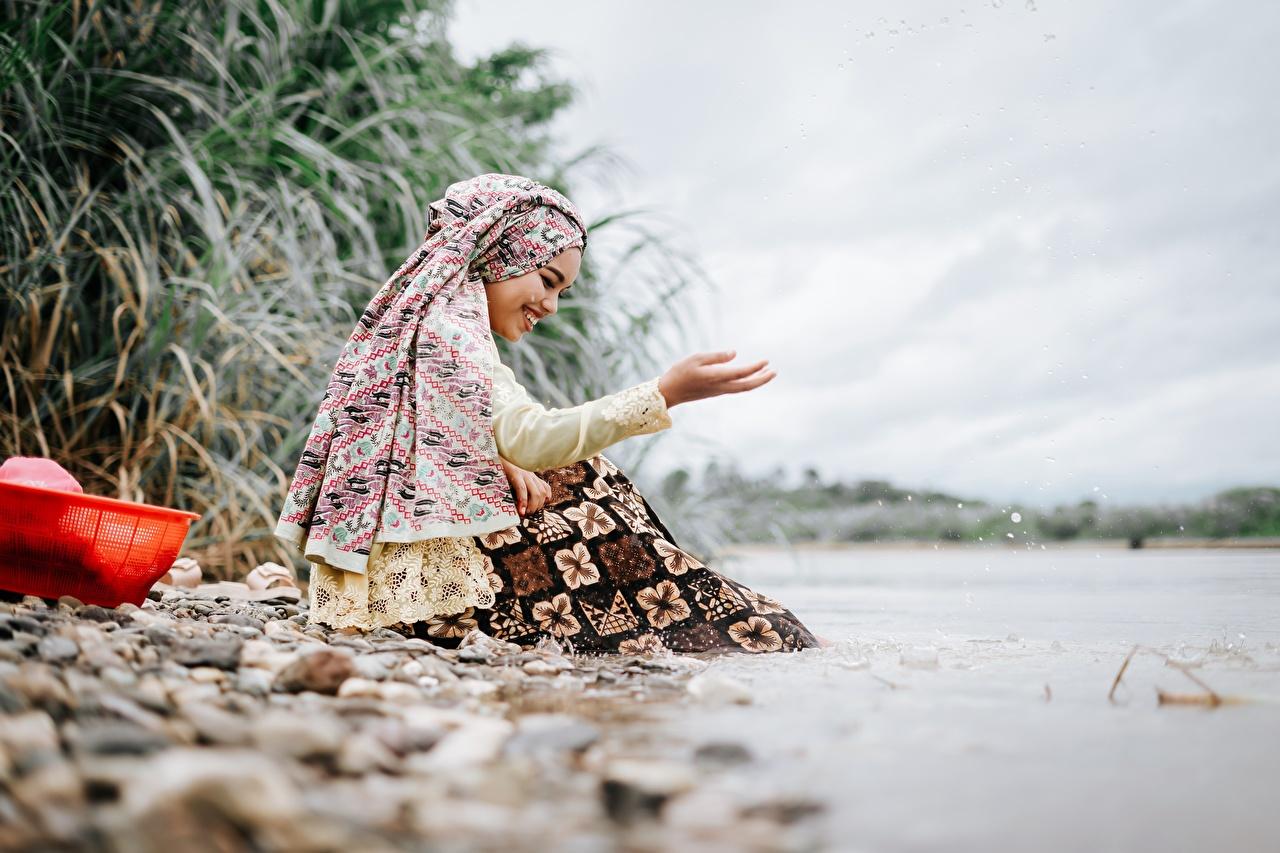 Фотография улыбается боке девушка азиатки Руки Камни Сидит Улыбка Размытый фон Девушки молодая женщина молодые женщины Азиаты азиатка сидя рука Камень сидящие