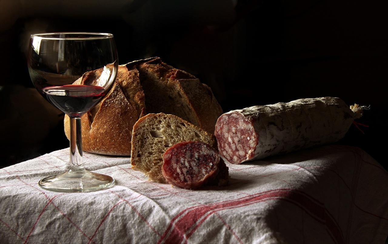 Фотографии Вино Колбаса Хлеб Пища бокал Черный фон Еда Бокалы Продукты питания на черном фоне