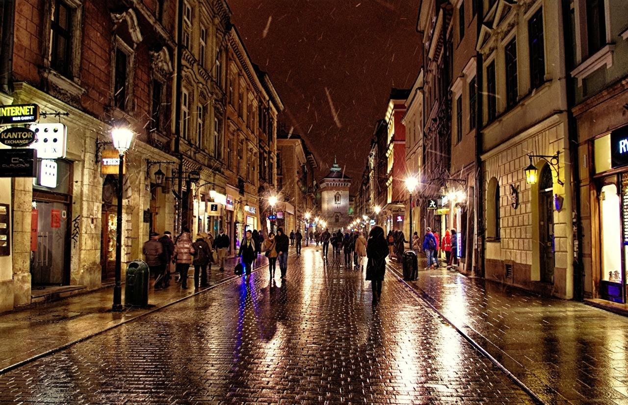 Обои для рабочего стола Польша Люди улице в ночи Тротуар Уличные фонари Города улиц Улица Ночь ночью Ночные город