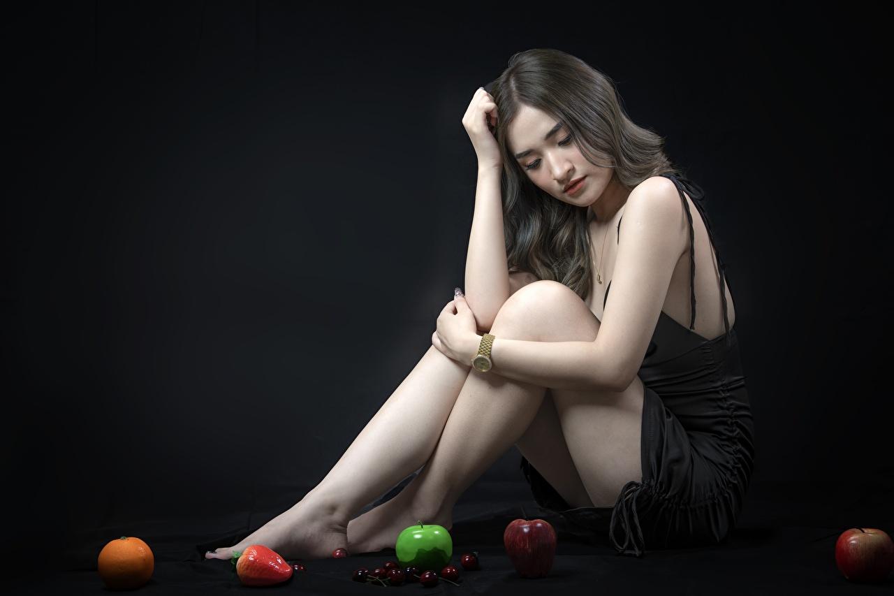 Фотографии брюнеток молодые женщины Ноги Яблоки азиатка Руки Сидит на черном фоне брюнетки Брюнетка девушка Девушки молодая женщина ног Азиаты азиатки рука сидя сидящие Черный фон