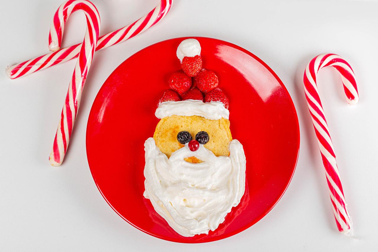 Картинки Рождество Блины шапка Леденцы сливками Санта-Клаус Креатив Клубника Еда Ягоды Тарелка сером фоне Новый год Шапки Сливки в шапке Дед Мороз креативные оригинальные Пища тарелке Продукты питания Серый фон