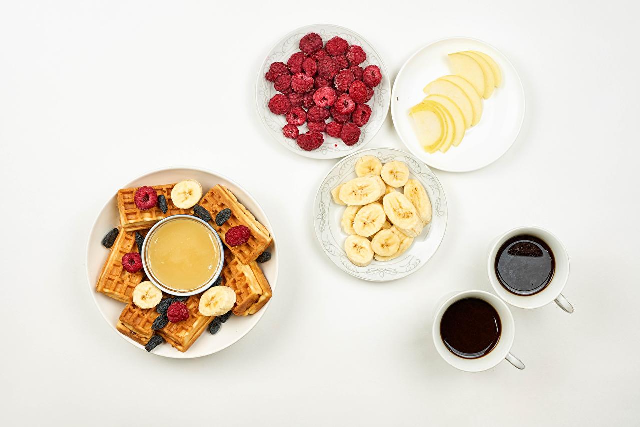 Фотографии вафля Мед Кофе Завтрак Малина Бананы Чашка тарелке Продукты питания Белый фон Вафли Еда Пища чашке Тарелка белом фоне белым фоном