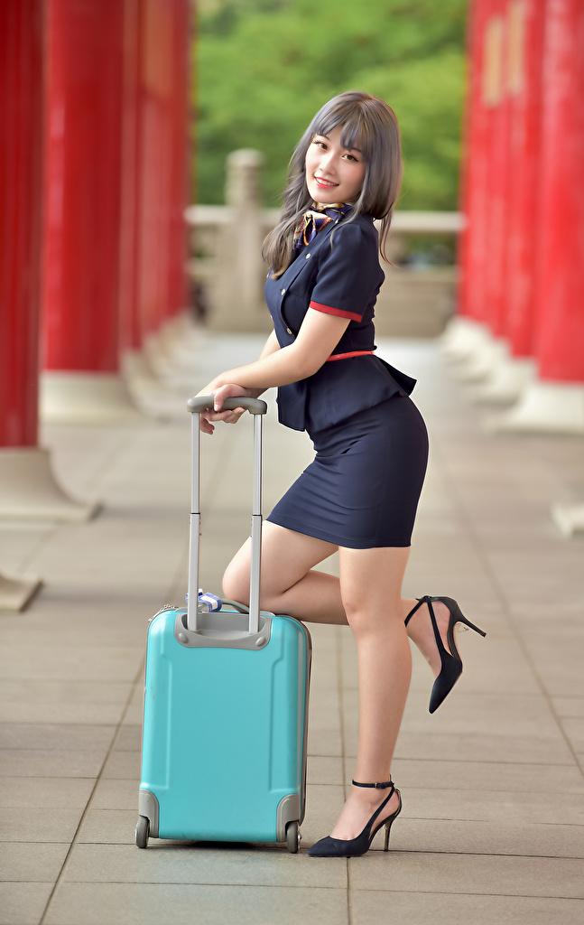 Фото Стюардессы позирует молодая женщина ног Азиаты Чемодан Униформа смотрит  для мобильного телефона стюардесс стюардесса Поза девушка Девушки молодые женщины Ноги азиатки азиатка чемоданы чемоданом униформе Взгляд смотрят