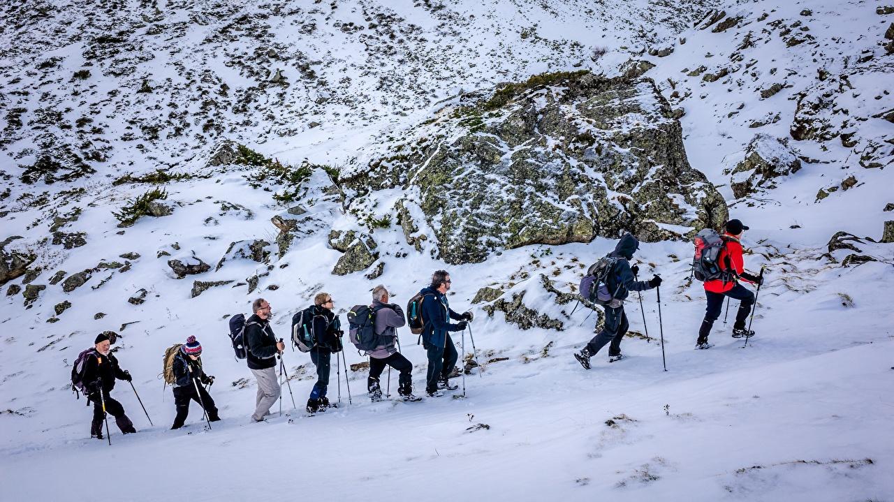 Фото Мужчины идет Горы Зима Природа Альпинизм Снег Очки Камни зимние гуляет Прогулка Камень