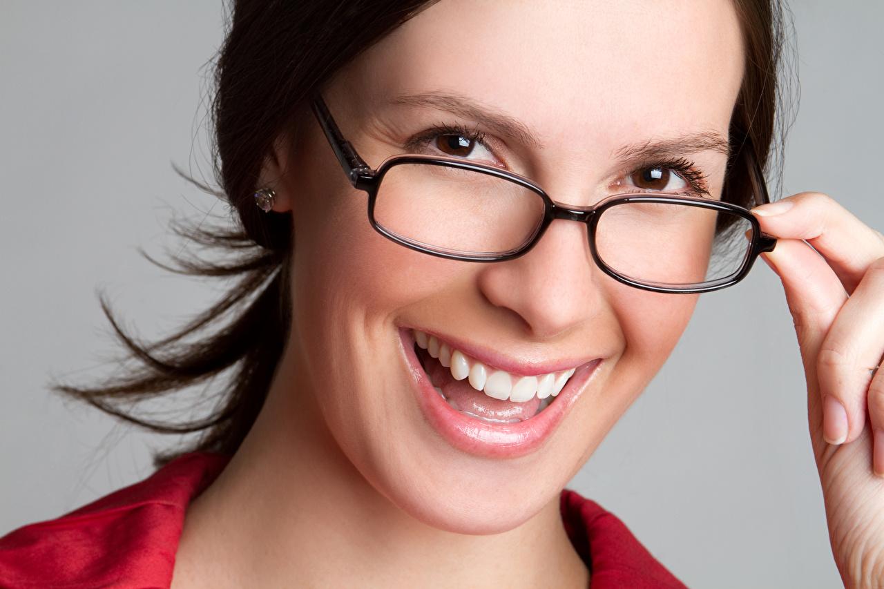 Фотография брюнетки Улыбка Лицо Девушки Зубы очках Пальцы Серый фон Брюнетка брюнеток улыбается лица девушка молодая женщина молодые женщины Очки очков сером фоне