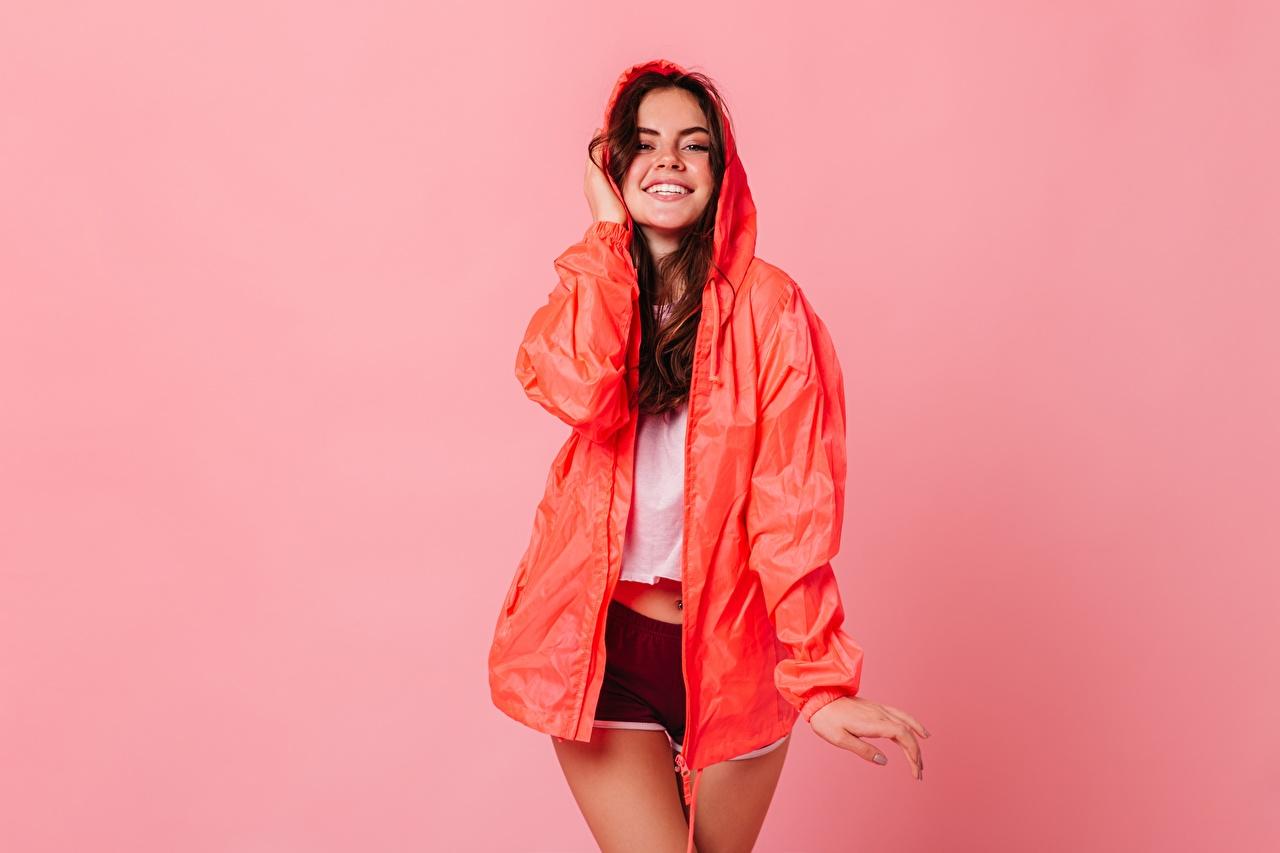 Фотографии Улыбка Поза девушка шортах плащом Цветной фон улыбается позирует Девушки молодая женщина молодые женщины шорт Плащ Шорты плаще