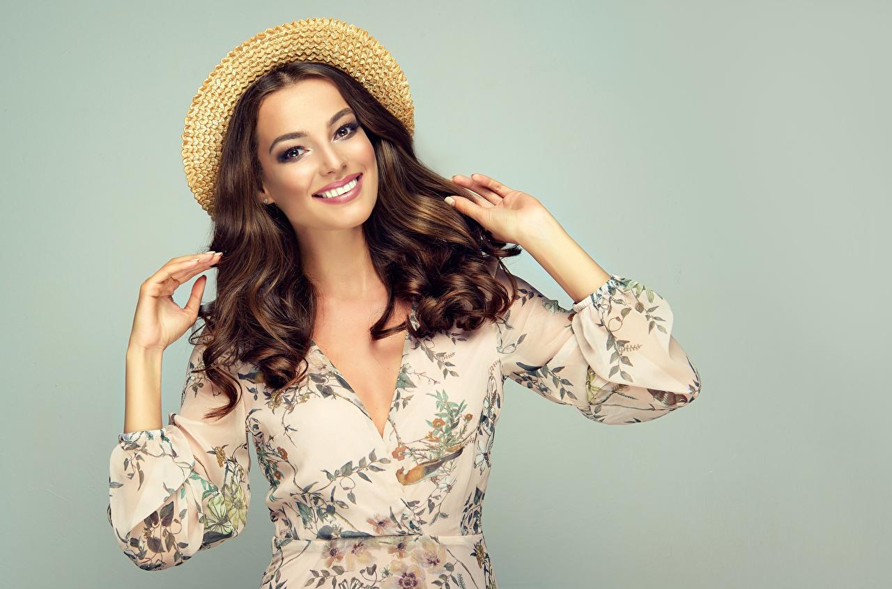 Обои для рабочего стола шатенки улыбается Причёска шляпе Волосы Девушки рука смотрит Серый фон Шатенка Улыбка прически шляпы волос Шляпа девушка молодые женщины молодая женщина Руки Взгляд смотрят сером фоне