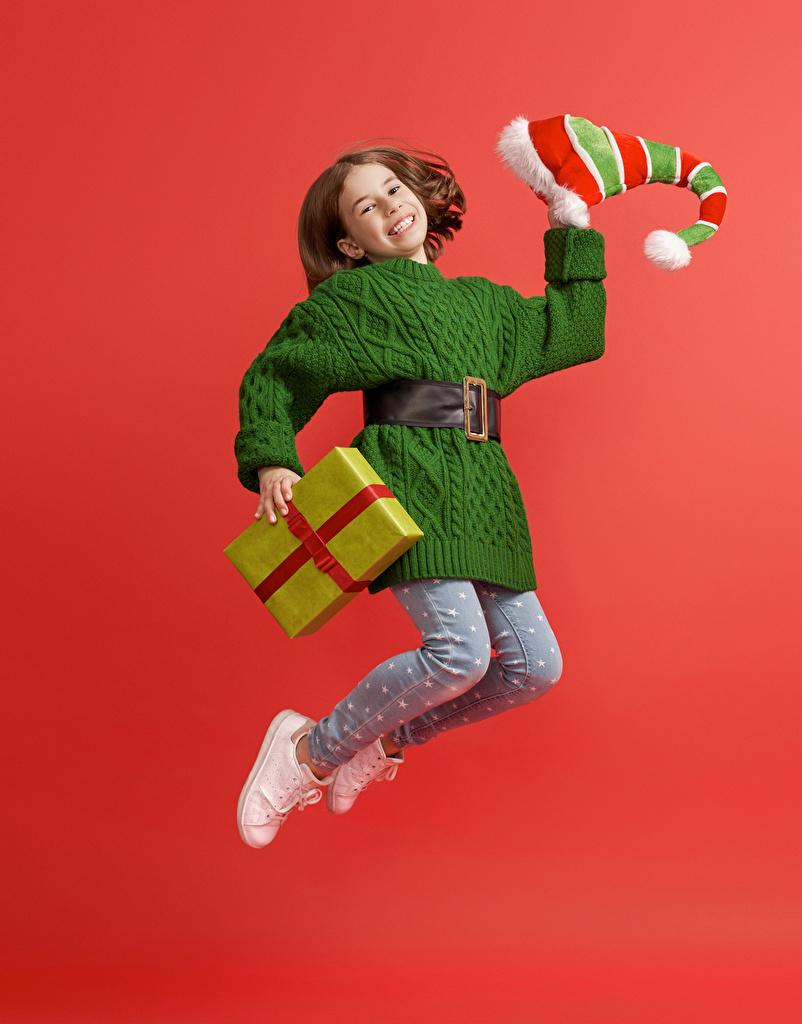 Картинки девочка Новый год Улыбка Дети шапка прыгает Подарки Красный фон Платье  для мобильного телефона Девочки Рождество улыбается ребёнок Шапки в шапке Прыжок прыгать подарок в прыжке подарков красном фоне платья