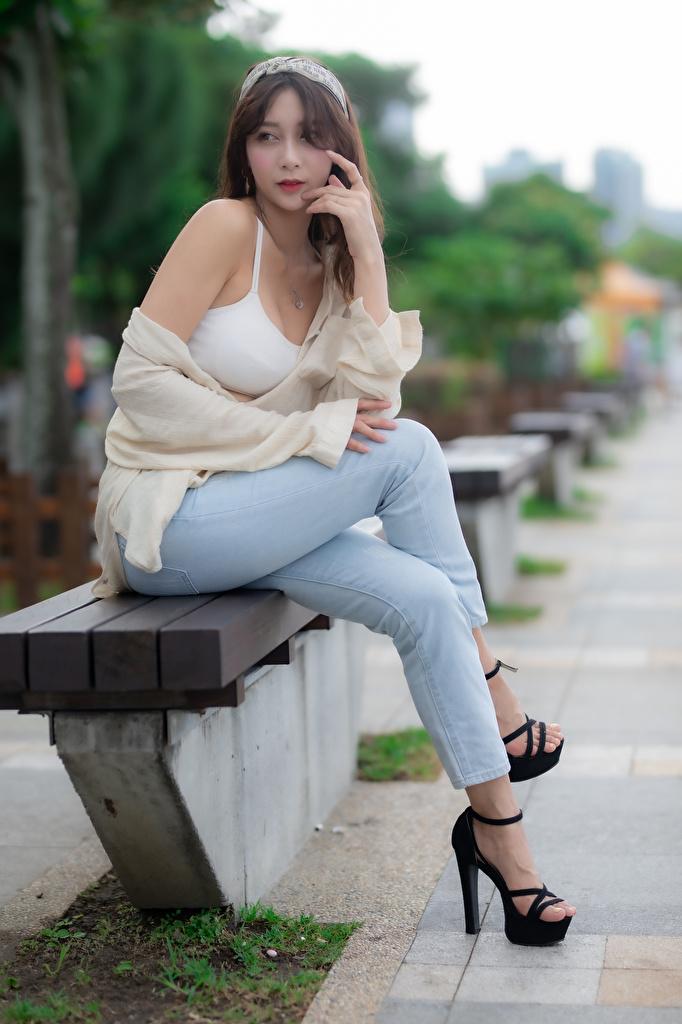 Картинки Размытый фон девушка Ноги азиатка джинсов Сидит  для мобильного телефона боке Девушки молодая женщина молодые женщины ног Азиаты Джинсы азиатки сидя сидящие