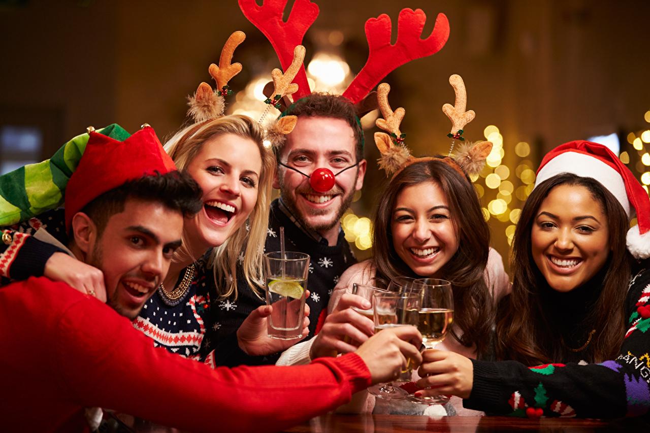 Фотографии Рождество Мужчины смеется счастливый с рогами Шапки Девушки Бокалы Праздники Новый год мужчина Смех Радость счастье смеются радостный радостная счастливые счастливая Рога шапка в шапке девушка молодые женщины молодая женщина бокал