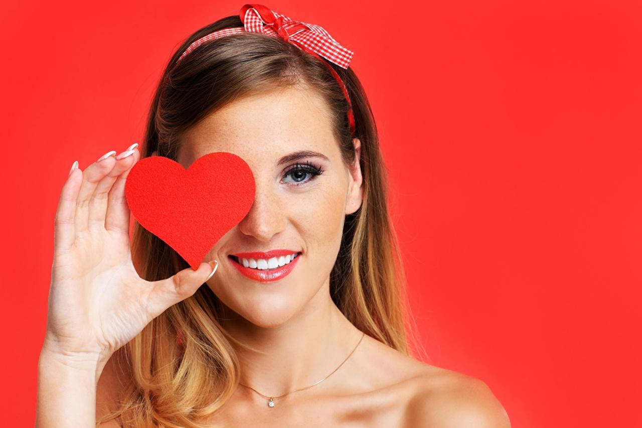 Картинки День святого Валентина Улыбка Сердце молодая женщина Руки красном фоне День всех влюблённых серце сердца сердечко улыбается девушка Девушки молодые женщины рука Красный фон