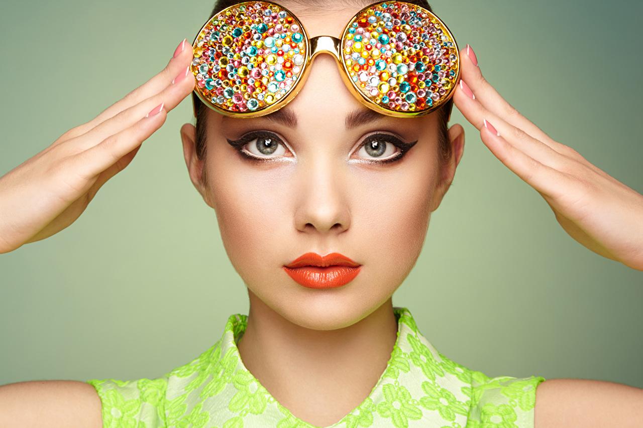 Фотография Макияж лица Девушки очках Пальцы смотрит сером фоне Красные губы мейкап косметика на лице Лицо девушка молодая женщина молодые женщины Очки очков Взгляд смотрят Серый фон красными губами