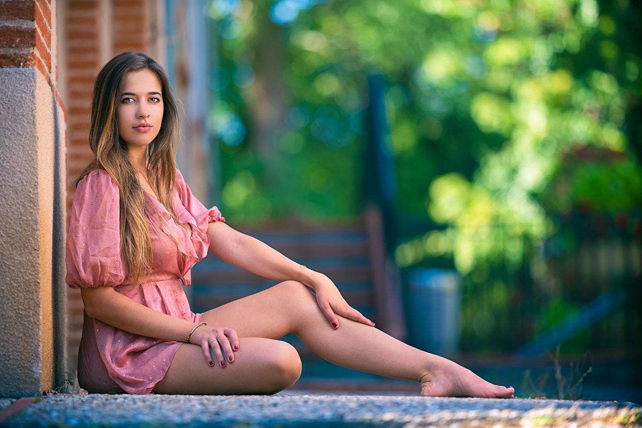 Обои для рабочего стола боке девушка Ноги Сидит Взгляд Платье Размытый фон Девушки молодые женщины молодая женщина ног сидя сидящие смотрят смотрит платья