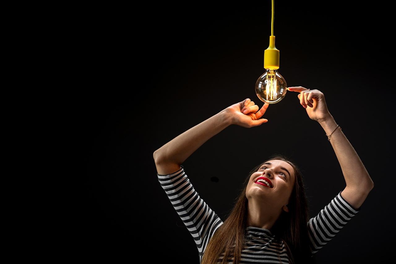 Фотографии шатенки улыбается девушка Лампочка Руки Черный фон Шатенка Улыбка Девушки молодая женщина молодые женщины лампа накаливания рука на черном фоне