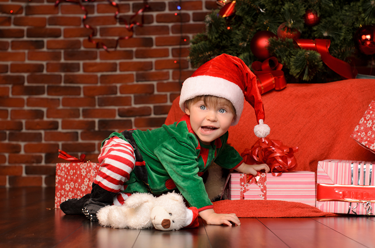 Картинка мальчик Рождество Дети в шапке подарков Стена униформе Взгляд Мальчики мальчишки мальчишка Новый год ребёнок Шапки шапка Подарки подарок стене стены стенка Униформа смотрят смотрит