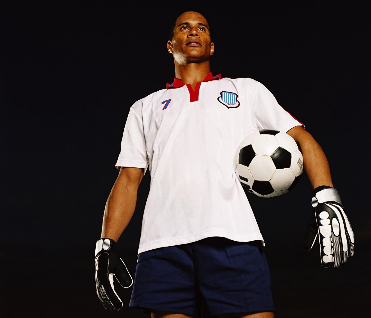 Фотографии мужчина Перчатки Футбол спортивные Мяч Униформа на черном фоне Мужчины перчатках Спорт спортивная спортивный Мячик униформе Черный фон