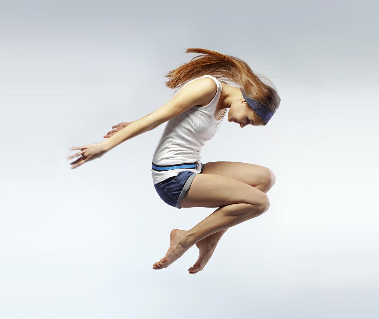 Фото Шатенка Девушки Майка в прыжке Руки сером фоне шатенки девушка молодые женщины молодая женщина майке майки Прыжок прыгать прыгает рука Серый фон