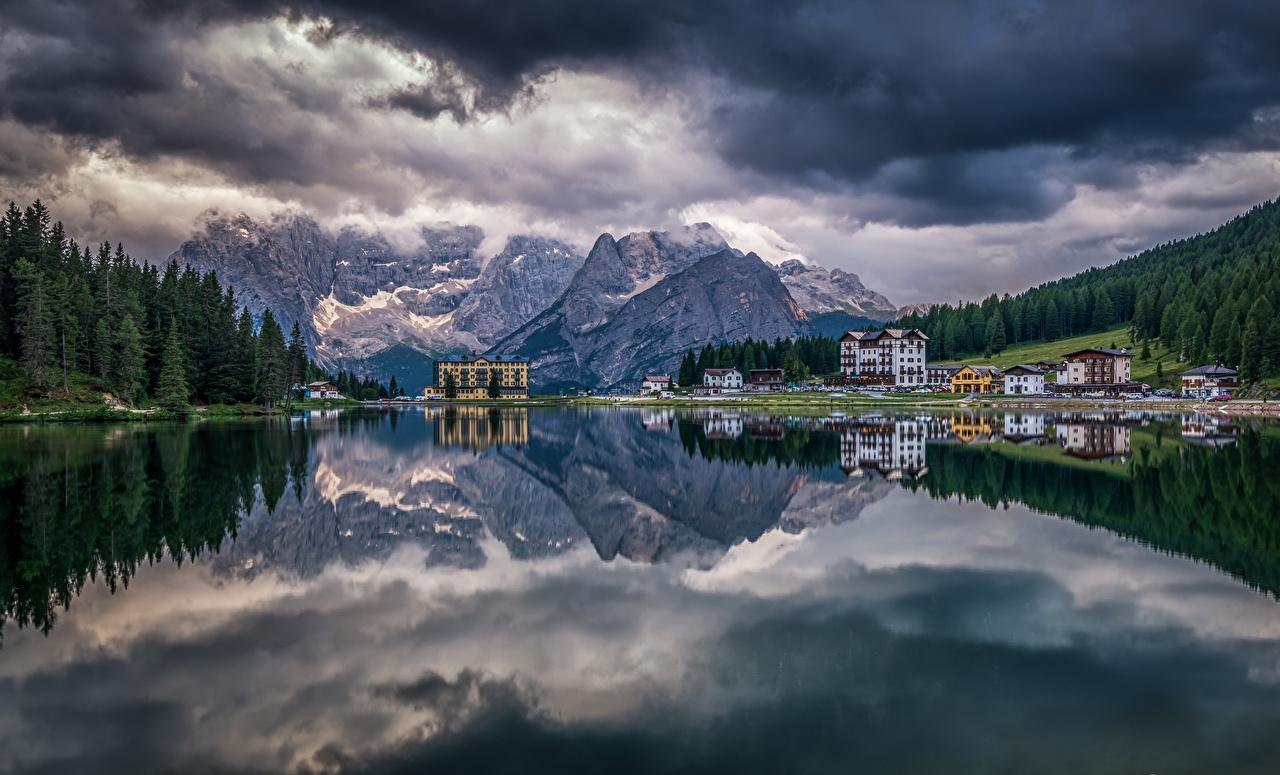 Фотография альп Италия Lake Misurina Горы Природа лес Озеро Пейзаж Дома облачно Альпы гора Леса облако Облака Здания
