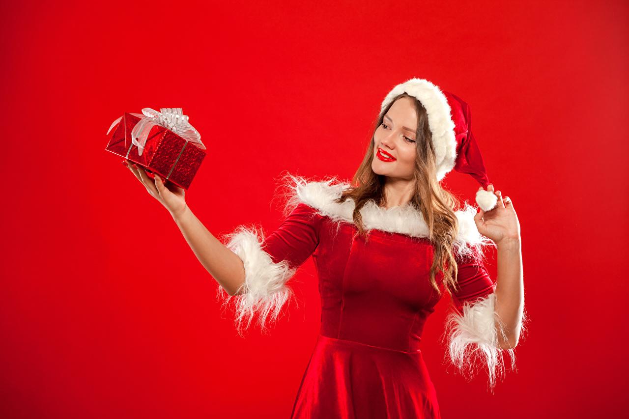 Обои Новый год Блондинка Шапки Девушки Подарки Руки Униформа Красный фон Рождество