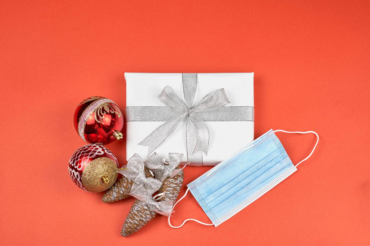 Фото Коронавирус Новый год подарок Шар Маски Шишки Бантик красном фоне Рождество Подарки подарков бант шишка Шарики бантики Красный фон