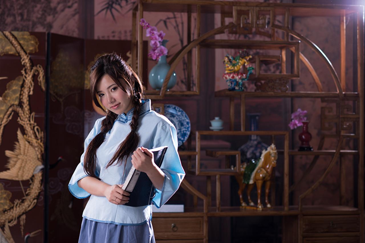Картинки Шатенка косы боке Тетрадь Девушки Азиаты рука смотрят шатенки Коса косички Размытый фон девушка молодая женщина молодые женщины азиатки азиатка Руки Взгляд смотрит