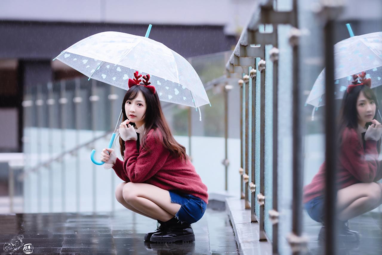 Фотографии Шатенка Размытый фон молодые женщины азиатка свитере Сидит зонтом шатенки боке девушка Девушки молодая женщина Свитер Азиаты азиатки свитера Зонт сидя зонтик сидящие