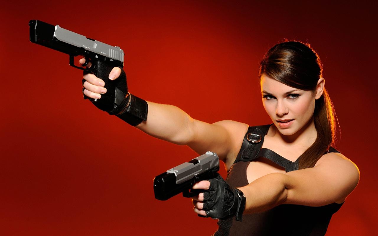 Картинка Лара Крофт пистолетом Косплей Перчатки Alison Carroll девушка Руки Взгляд Красный фон пистолет Пистолеты перчатках Девушки молодая женщина молодые женщины рука смотрят смотрит красном фоне
