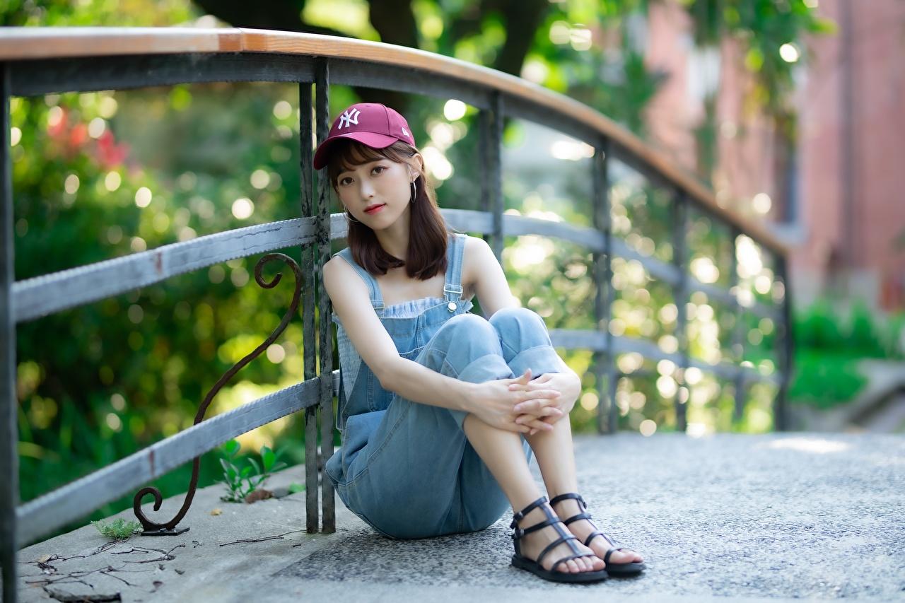 Картинка Шатенка боке молодая женщина Ноги Забор Азиаты сидя рука Кепка шатенки Размытый фон девушка Девушки молодые женщины ног ограда забора азиатки азиатка забором Руки Сидит сидящие кепке кепкой Бейсболка