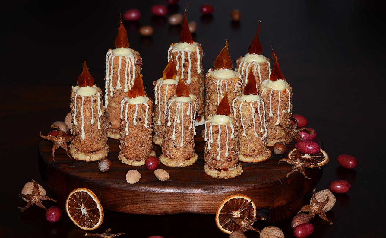 Фото Еда Свечи Орехи Пирожное сладкая еда на черном фоне дизайна Пища Продукты питания Сладости Черный фон Дизайн
