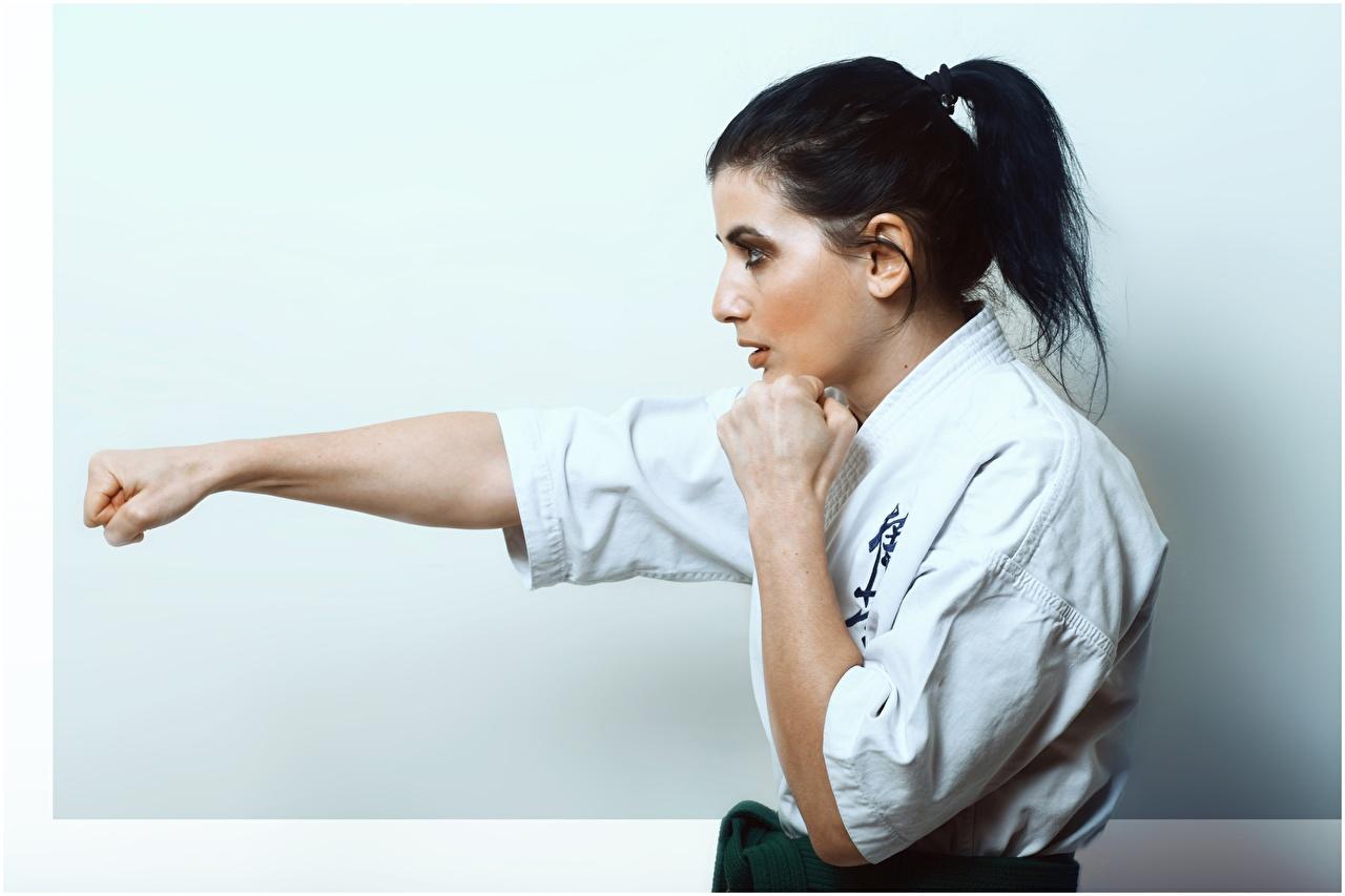 Обои для рабочего стола молодые женщины Сбоку брюнеток Karate рука Бьет Кулак девушка Девушки молодая женщина брюнетки Брюнетка Руки Удар Ударяет