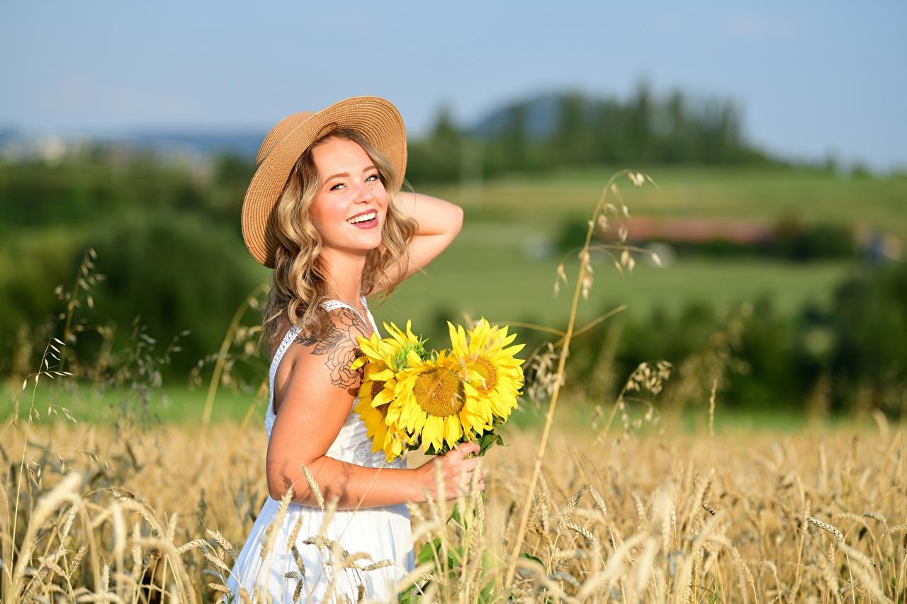 Фотография блондинки Улыбка боке Лето Шляпа девушка Поля Подсолнечник Платье Блондинка блондинок улыбается Размытый фон шляпы шляпе Девушки молодая женщина молодые женщины Подсолнухи платья