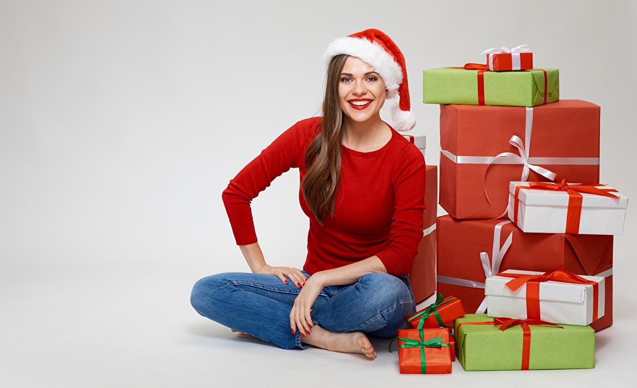 Картинки Шатенка Новый год улыбается шапка девушка Подарки сидя Взгляд Серый фон шатенки Рождество Улыбка Шапки в шапке Девушки молодые женщины молодая женщина подарок подарков Сидит сидящие смотрит смотрят сером фоне