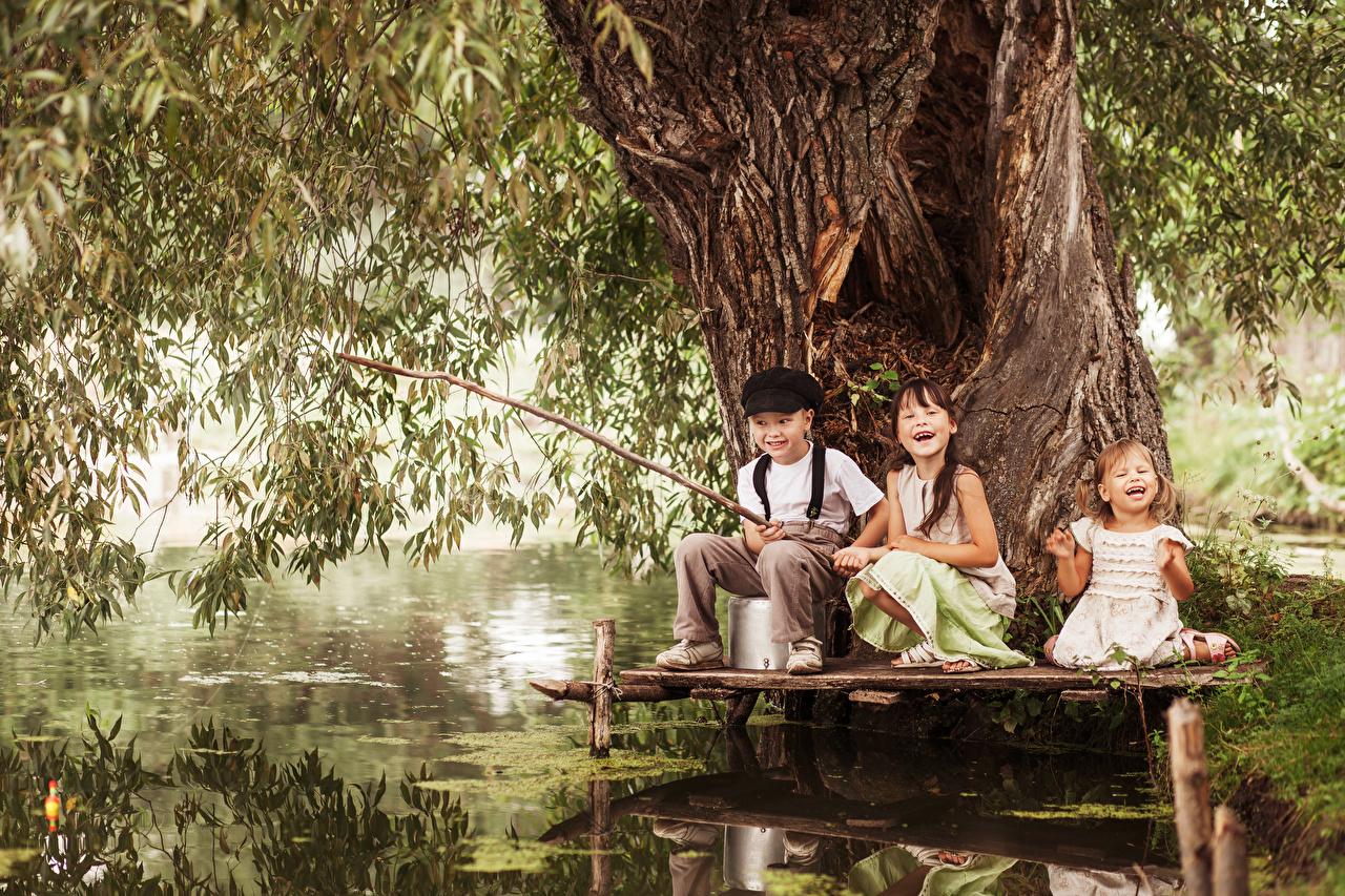 Фото Девочки Мальчики счастье ребёнок Рыбалка Ствол дерева Трое 3 девочка мальчик мальчишки мальчишка Радость радостная радостный счастливые счастливая счастливый Дети ловля рыбы три втроем