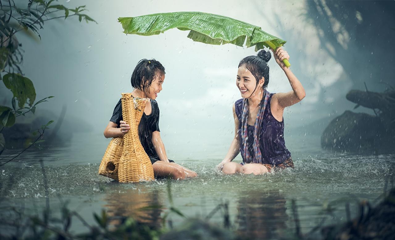 Фотография Девочки Листва Смех Дети Двое Дождь Азиаты сидящие Мокрые Листья Ребёнок 2 вдвоем Сидит