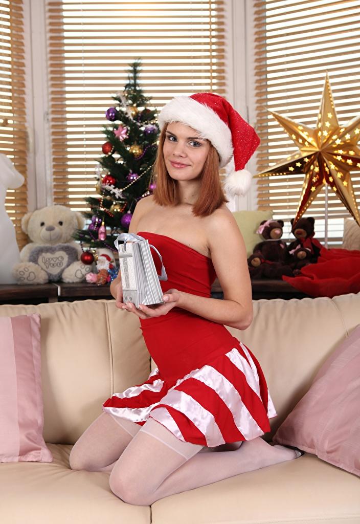 Картинки Рыжая Рождество Улыбка Шапки Девушки Новогодняя ёлка Подарки Диван смотрит Новый год Елка Взгляд