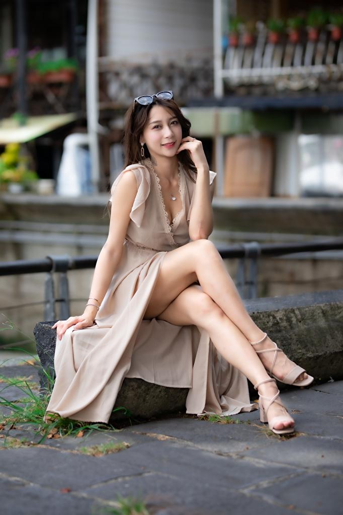 Фото боке девушка Ноги Азиаты Сидит смотрит Платье  для мобильного телефона Размытый фон Девушки молодая женщина молодые женщины ног азиатки азиатка сидя сидящие Взгляд смотрят платья