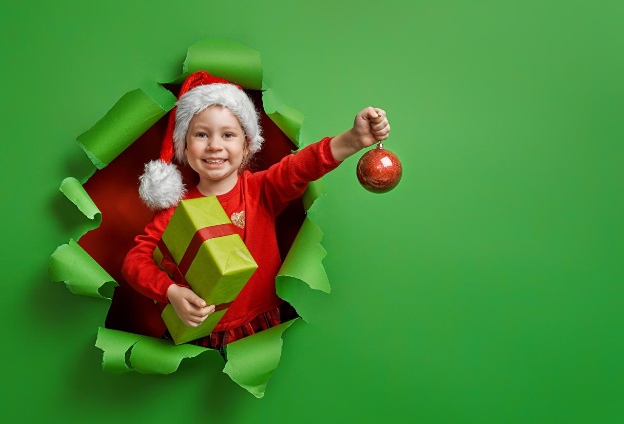 Картинка девочка Новый год Улыбка Дети Шапки подарков Шар Руки Цветной фон Девочки Рождество улыбается ребёнок шапка в шапке Подарки подарок рука Шарики