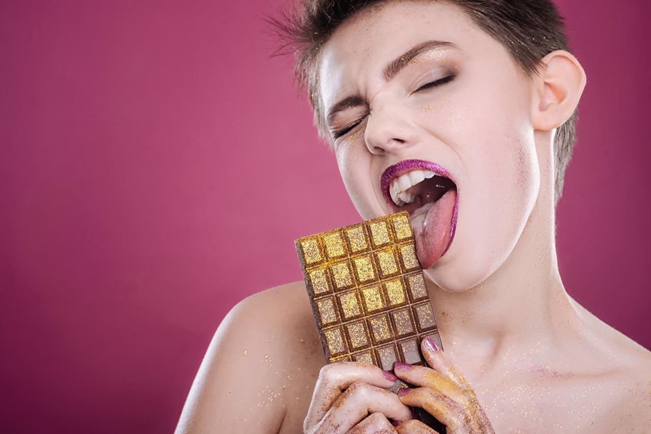 Картинки Шатенка Шоколадная плитка Шоколад Девушки Язык (анатомия) Пальцы Цветной фон шоколадка