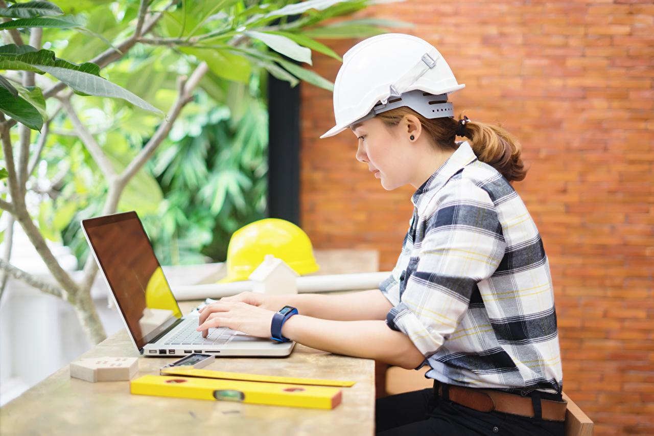 Картинка ноутбук шлема Работа construction helmet Девушки сидя Сбоку Ноутбуки Шлем в шлеме работает работают девушка молодая женщина молодые женщины Сидит сидящие