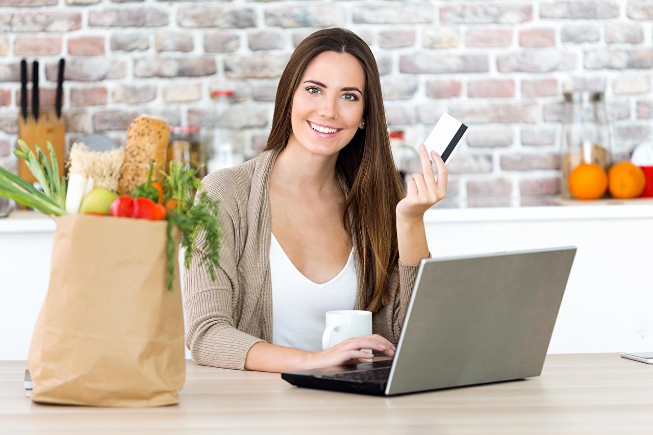 Картинка Ноутбуки Шатенка купили Улыбка Бумажный пакет молодая женщина смотрит Компьютеры ноутбук шатенки покупка Покупки покупать улыбается девушка Девушки молодые женщины Взгляд смотрят