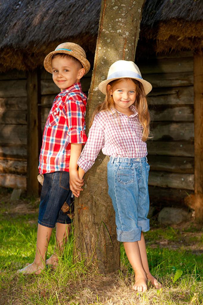 Фото Девочки Мальчики Улыбка Ребёнок 2 Шляпа Ствол дерева Дети Двое вдвоем