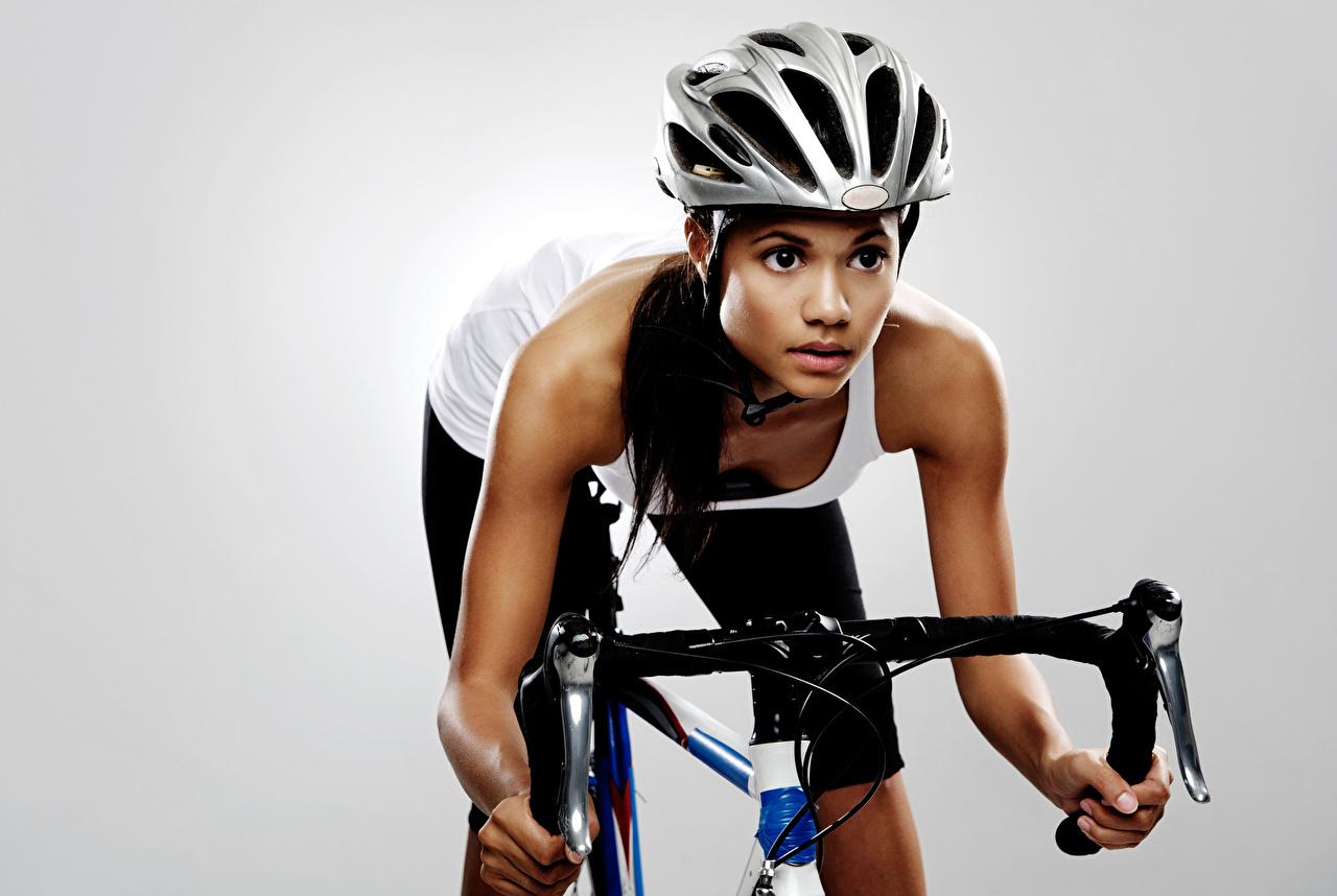 Фотография в шлеме Велосипедный руль спортивная молодые женщины Взгляд сером фоне Шлем шлема Спорт девушка Девушки спортивные спортивный молодая женщина смотрят смотрит Серый фон