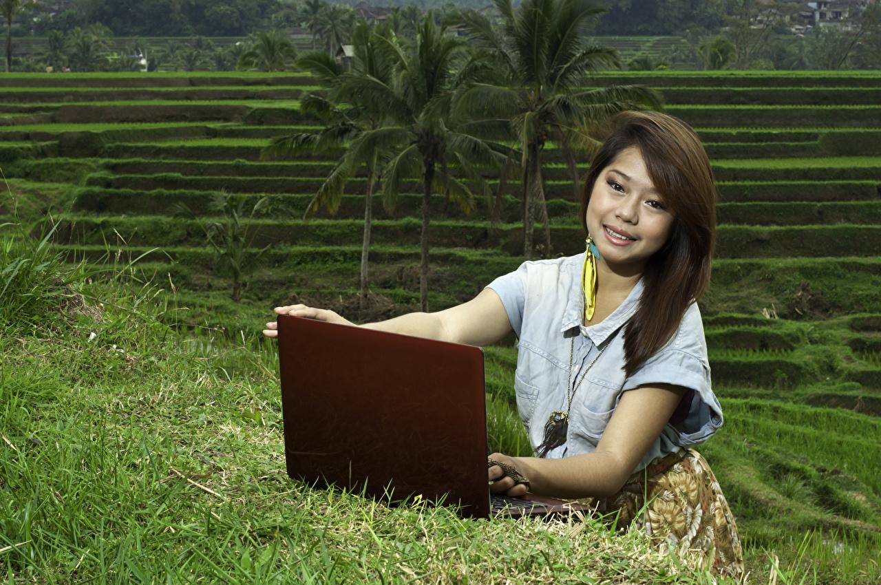 Картинки Ноутбуки шатенки улыбается молодая женщина азиатки смотрят ноутбук Шатенка Улыбка девушка Девушки молодые женщины Азиаты азиатка Взгляд смотрит