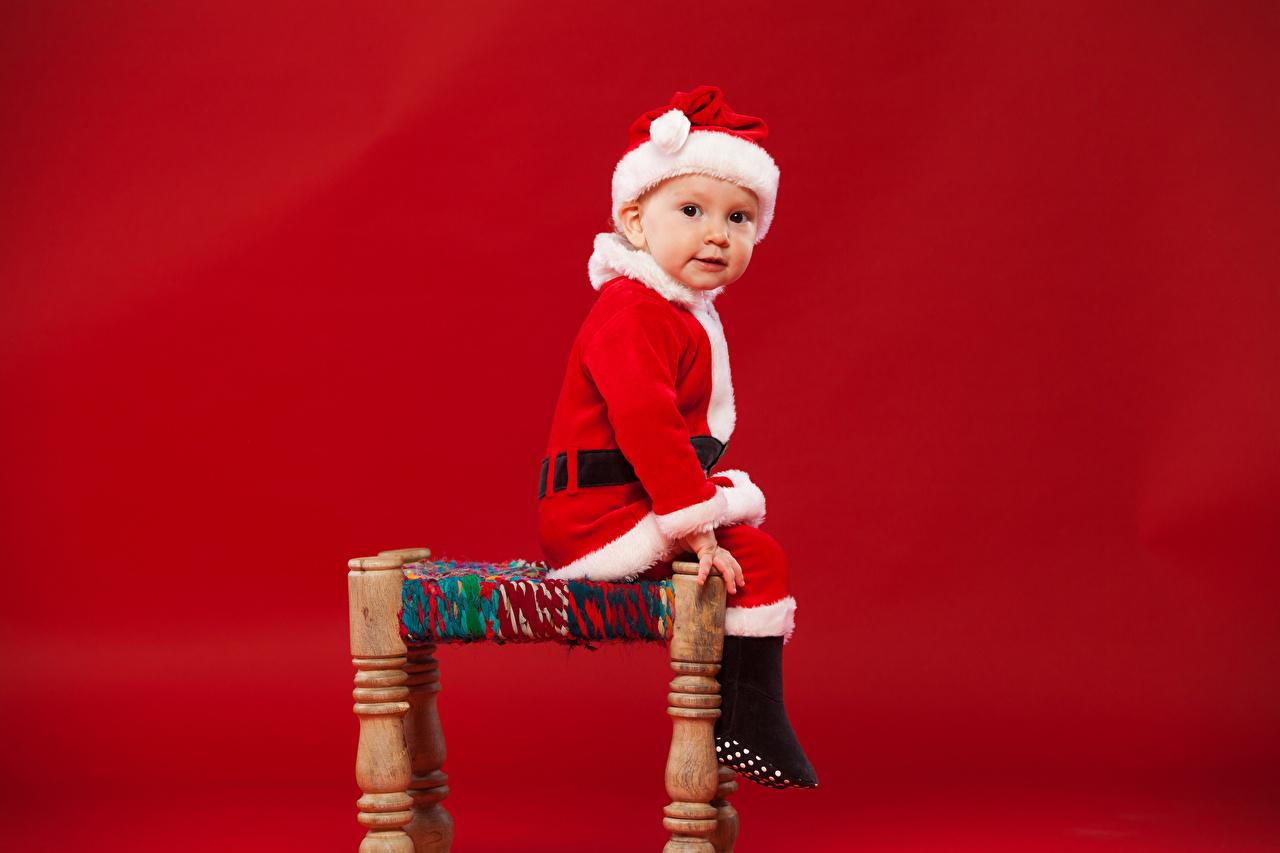 Фотографии Мальчики Рождество Дети шапка Дед Мороз сидя смотрит Красный фон мальчик мальчишки мальчишка Новый год ребёнок Шапки в шапке Санта-Клаус Сидит сидящие Взгляд смотрят красном фоне