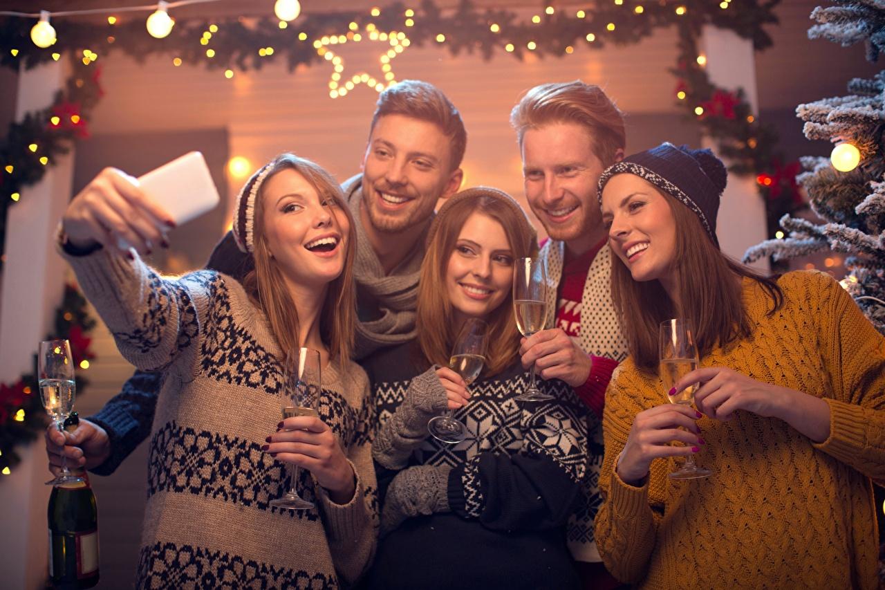 Фотография Рождество Мужчины Селфи Улыбка в шапке Девушки Свитер рука Бокалы Новый год мужчина улыбается шапка Шапки девушка молодая женщина молодые женщины свитере свитера Руки бокал