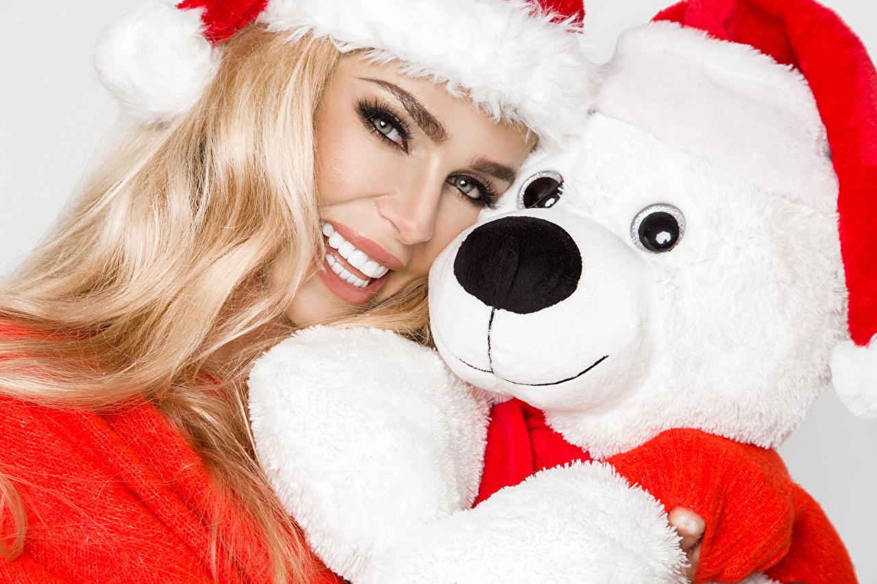 Фото блондинок Рождество Улыбка Шапки девушка Плюшевый мишка смотрят Новый год Блондинка блондинки улыбается шапка в шапке Девушки молодые женщины молодая женщина Мишки Взгляд смотрит